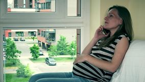 Unhappy female expectant showing negative emotions on phone. Frustrated pregnant woman talking on phone. Unhappy female expectant showing negative emotions stock video footage