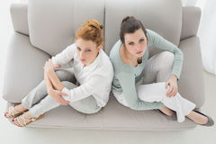 Unhappy female friends not talking after argument on the couch Stock Photo