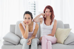 Unhappy female friends not talking after argument on couch Royalty Free Stock Images