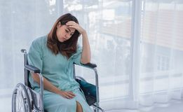 Unhappy female patient worry about her medical fee. A portrait of unhappy female patient sitting on wheelchair in hospital room. She worry about her medical fee stock photos