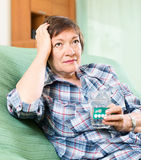 Unhappy female pensioner with pills and glass of water Royalty Free Stock Photography