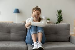 Unhappy female sit on couch feeling sad at home. Unhappy female sit on sofa feeling lonely and sad, upset girl crying at home having relationships or life royalty free stock images
