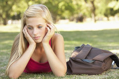 Unhappy Female Teenage Student In Park royalty free stock images
