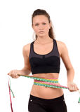 Unhappy fit girl measuring her waist with three measuring tapes. Stock Image