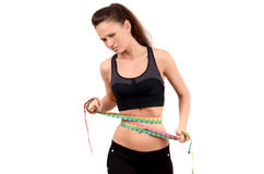 Unhappy fit girl measuring her waist with three measuring tapes. Royalty Free Stock Photography