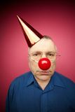 Unhappy fool�s day. Portrait of unhappy man with a red nose and in a cone cap on fool�s day Stock Image