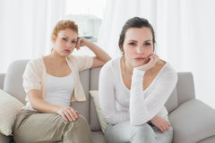 Unhappy friends not talking after argument on the couch Stock Photo