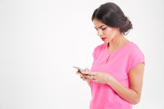 Unhappy frowning young woman using smartphone Stock Photos
