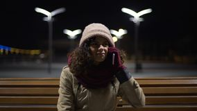 Unhappy frozen girl sitting outdoors, cannot reach guy by phone, failed date. Stock footage stock footage