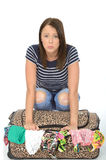 Unhappy Frustrated Attractive Young Woman Sitting on an Overflowed Suitcase Royalty Free Stock Photo