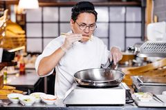 Unhappy frustrated chef smelling overcooked dish. Bad chef. unexperienced man cooking something in the kithcen room. failure while preparing meal royalty free stock photo