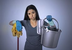 Unhappy and frustrated housekeeping woman holding mop and wash bucket as hotel cleaner service or house maid. Portrait of young beautiful unhappy and frustrated stock photography