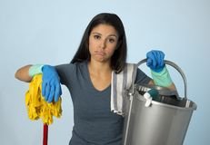 Unhappy and frustrated housekeeping woman holding mop and wash bucket as hotel cleaner service or house maid. Portrait of young beautiful unhappy and frustrated Royalty Free Stock Image