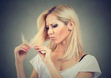 Unhappy frustrated woman surprised she has slit ends and losing hair. Beauty hairstyle concept royalty free stock images