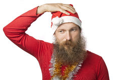Unhappy funny santa claus with real beard and red hat and shirt looking at camera with sadness. isolated on white Royalty Free Stock Photography