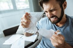Unhappy furious man tearing apart crumpled paper. Too emotional. Unhappy sad furious man tearing apart crumpled paper and screaming while showing his fury Stock Photography