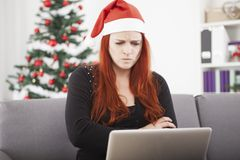 Unhappy girl is angry on the laptop. Unhappy young red haired girl with santa hat is angry on the laptop for christmas Stock Images