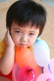 Unhappy girl with balloons. Sitting on the floor Stock Photo