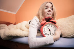 Unhappy girl in bed with alarm clock Stock Photo