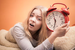 Unhappy girl in bed with alarm clock stock photography
