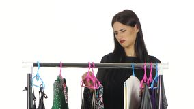 Unhappy girl chooses dress in the shop. White stock video