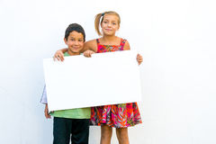Unhappy girl with happy boy holding banner Royalty Free Stock Photography