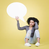 Unhappy girl holding a white speech balloon with copyspace. Stock Images