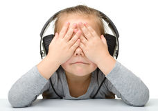Unhappy girl listening music using headphones Stock Photography