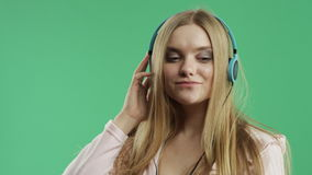 Unhappy girl listening to music on headphones stock video