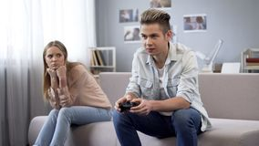 Unhappy girl looking at her boyfriend who indifferently playing video games. Stock photo royalty free stock images