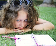 Unhappy girl lying on the grass with notebook stock images