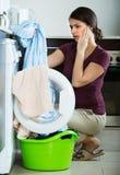 Unhappy girl near washing machine Stock Photo