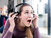 Unhappy girl in pain screaming in removing her headphones home Stock Photo