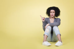 Unhappy girl pointing up at copy space. stock image
