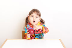 Unhappy girl with red apple at the desk Stock Photo