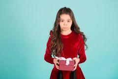 Unhappy girl in red dress hold present box. Unhappy girl with long brunette hair in red dress hold present box on blue background. Boxing day concept. Birthday Stock Images
