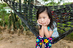 Unhappy girl sitting alone in hammock.. Outdoor on summer day. Unhappy girl propping up her face and sitting alone in hammock. Asian child bored, frustrated and Stock Images