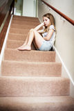Unhappy Girl Sitting On Stairs At Home Royalty Free Stock Image