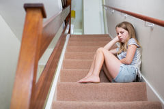 Unhappy Girl Sitting On Stairs At Home Royalty Free Stock Photos