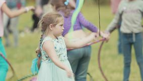 Unhappy girl spinning flying ribbons on grass at summer outdoor festival. Unhappy caucasian girl spinning flying ribbons on grass at crowded summer outdoor stock video footage