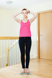 Unhappy girl standing on bathroom scales. At home interior Stock Photography