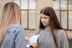 Unhappy girl is standing near the university and look at the adult with paper stock photography