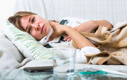 Unhappy girl suffering of sore throat. And fever at home Royalty Free Stock Images