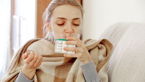 Unhappy girl suffering of sore throat and fever. Young brunette sick with fever under blanket in domestic interior stock footage