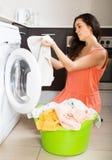 Unhappy  girl using washing machine at home Royalty Free Stock Photos