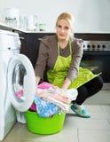 Unhappy girl using washing machine Royalty Free Stock Photo