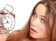Unhappy girl waking up too late. And looking at the alarm clock. Isolated over white background Stock Photos