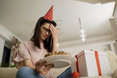 An unhappy girl wearing a hat on her birthday with a cake  is al. An unhappy girl wearing a hat on her birthday with a cake with candles is alone in the room Royalty Free Stock Photography