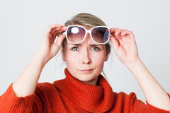 Unhappy girl wearing winter sweater trying sunglasses Royalty Free Stock Image