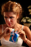 Unhappy girl in a wedding dress tearing pictures. Stock Images